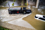 A Houston Police Water Rescue vehicle mobilizes by a stranded by flood car on Houston Ave., during Tropical Storm Beta, Tuesday, Sept. 22, 2020, in Houston. Beta has weakened to a tropical depression as it parked itself over the Texas coast, raising concerns of extensive flooding in Houston and areas further inland. (Marie D. De Jesus/Houston Chronicle via AP)