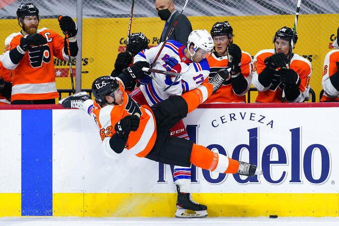 Philadelphia Flyers' Nicolas Aube-Kubel (62) and New York Rangers' Kevin Rooney (17) collide during the first period of an NHL hockey game, Thursday, March 25, 2021, in Philadelphia. (AP Photo/Matt Slocum)