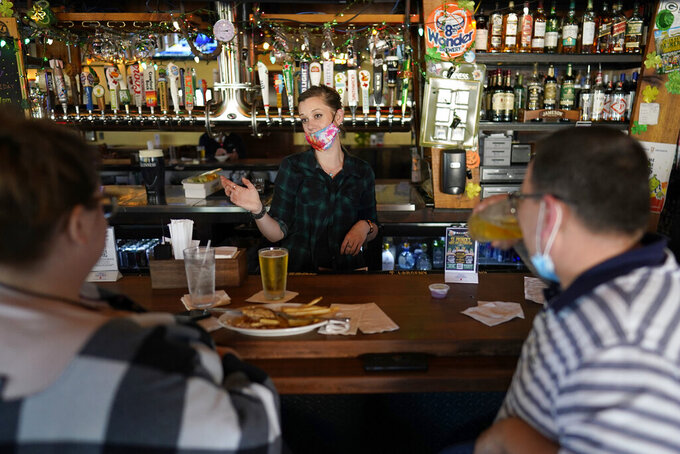 Bartender Alyssa Dooley, center, talks with customers at Mo's Irish Pub, Tuesday, March 2, 2021, in Houston. Texas Gov. Greg Abbott announced that he is lifting business capacity limits and the state's mask mandate starting next week. (AP Photo/David J. Phillip)