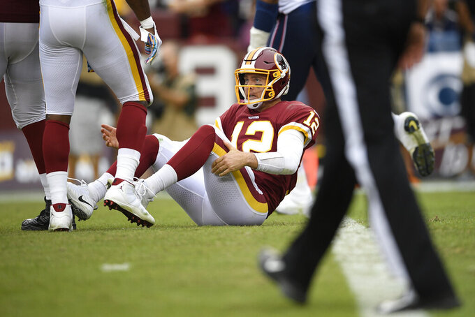 Washington Redskins quarterback Colt McCoy (12) sits on ther field after a New England Patriots sack during the second half of an NFL football game, Sunday, Oct. 6, 2019, in Washington. (AP Photo/Nick Wass)