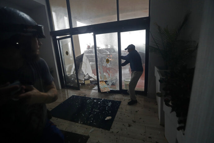 FILE - In this Oct. 10, 2018 file photo, a hotel employee holds a glass door closed as it breaks from flying debris during Hurricane Michael in Panama City Beach, Fla. The tropical weather that turned into monster Hurricane Michael began as a relatively humble storm before rapidly blossoming into the most powerful cyclone ever to hit the Florida Panhandle, causing wrenching scenes of widespread destruction. (AP Photo/Gerald Herbert, File)