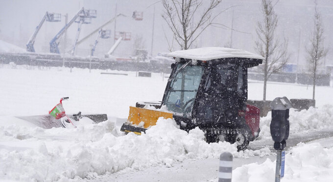 A maintenance worker uses a plow as a snowstorm rips across the intermountain West Sunday, March 14, 2021, in Denver. Forecasters are calling for the storm to leave at least another six inches of snow during the day before moving out on to the eastern plains. (AP Photo/David Zalubowski)