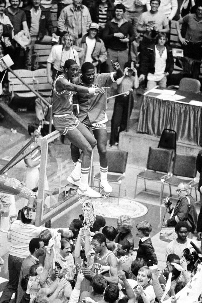 FILE - In this April 5, 1983, file photo, North Carolina State players Cozell McQueen, left, and Ernie Myers celebrate while standing on the rim after defeating Houston 54-52 to win the NCAA college basketball championship in Albuquerque, N.M. (AP Photo/File)
