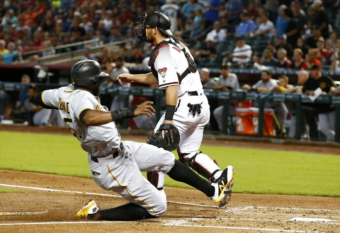 Pittsburgh Pirates' Gregory Polanco, left, scores a run as Arizona Diamondbacks catcher Jeff Mathis, right, waits for a late throw during the second inning of a baseball game Wednesday, June 13, 2018, in Phoenix. (AP Photo/Ross D. Franklin)