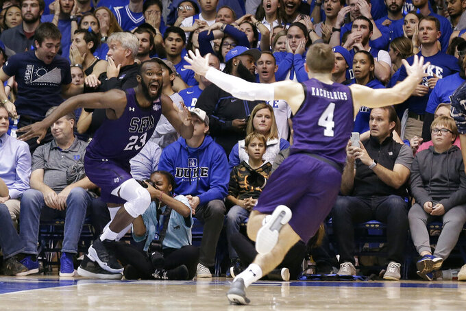 FILE - Stephen F. Austin forward Nathan Bain (23), of the Bahamas, and guard David Kachelries (4) celebrate Bain's game-winning basket against Duke in overtime of an NCAA college basketball game in Durham, N.C., in this Tuesday, Nov. 26, 2019, file photo. Bain provided one of college basketball's signature moments last season, a buzzer-beating layup in overtime to give unheralded Stephen F. Austin a stunning upset over Duke. But that became just a sliver of the story that night. His layup won a game -- and rebuilt a home, rebuilt a school and rebuilt a church, all of it directly impacting the lives of hundreds of Bahamians who have dealt with enormous challenges for the last 14 months and counting. (AP Photo/Gerry Broome, File)