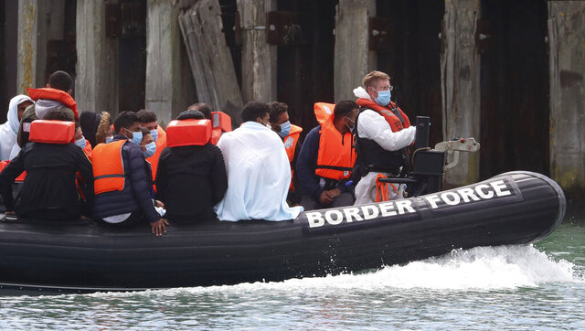 A British Border Force vessel carries a group of men thought to be migrants into Dover harbour, Southern England, Tuesday Aug. 4, 2020.  A number of incidents involving small boats crossing The Channel to Britain are reported over the past few days, as migrants take advantage of warm calm weather to cross the busy shipping lanes. (Gareth Fuller/PA via AP)