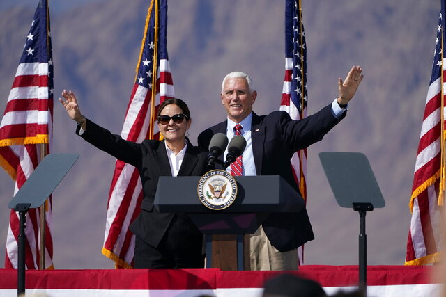 Vice President Mike Pence and second lady Karen Pence wave to the crowd during a campaign event Thursday, Oct. 8, 2020, in Boulder City, Nev. (AP Photo/John Locher)