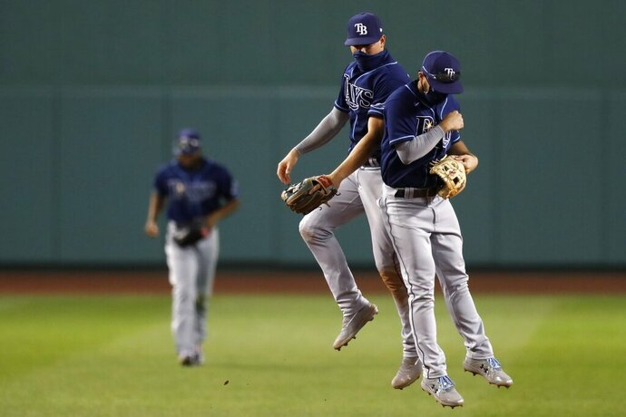 Tampa Bay Rays' Brandon Lowe, right, and Willy Adames celebrate after defeating the Boston Red Sox during a baseball game, Thursday, Aug. 13, 2020, in Boston. (AP Photo/Michael Dwyer)