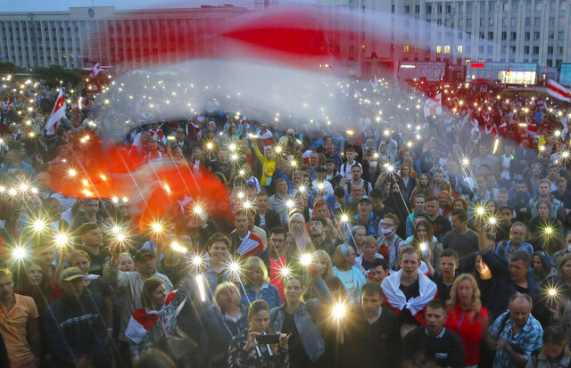 Belarusian opposition supporters light phones lights and wave an old Belarusian national flags during a protest rally in front of the government building at Independent Square in Minsk, Belarus, Wednesday, Aug. 19, 2020. The authoritarian leader of Belarus complained that encouragement from abroad has fueled daily protests demanding his resignation as European Union leaders held an emergency summit Wednesday on the country's contested presidential election and fierce crackdown on demonstrators. (AP Photo/Dmitri Lovetsky)