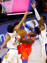 Oklahoma City Thunder's Luguentz Dort, center, passes around Phoenix Suns' Devin Booker (1) and Deandre Ayton (22) during the third quarter of an NBA basketball game Monday, Aug. 10, 2020, in Lake Buena Vista, Fla. (Mike Ehrmann/Pool Photo via AP)
