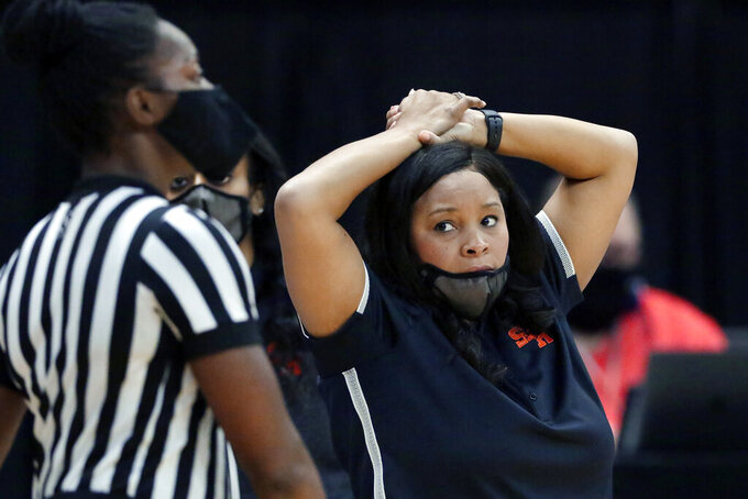 Sam Houston State head coach Ravon Justice looks at an official after a foul call during the first half of an NCAA college basketball game against Stephen F. Austin for the Southland Conference women's tournament championship Sunday, March 14, 2021, in Katy, Texas. (AP Photo/Michael Wyke)