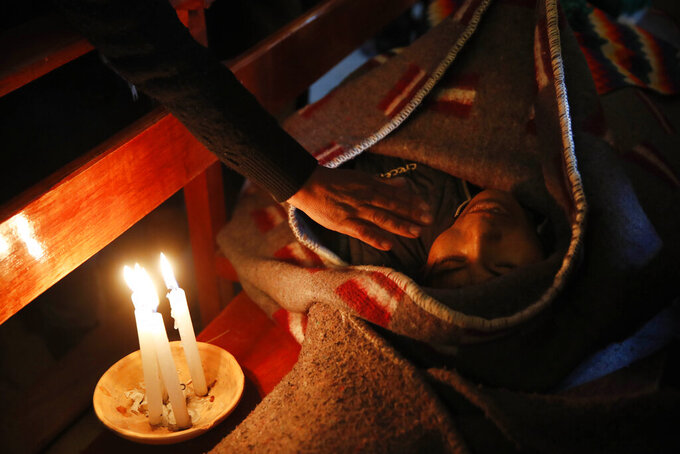 In this Wednesday, Nov. 20, 2019 photo, a mourner places a hand on the shoulder of Devi Posto killed during clashes between security forces and supporters of former President Evo Morales, during a vigil at the San Francisco de Asis church in El Alto, on the outskirts of La Paz, Bolivia. The death toll from an operation by Bolivian security forces to clear the blockade of a fuel plant by anti-government protesters has risen to six the public defender's office announced Wednesday.(AP Photo/Natacha Pisarenko)