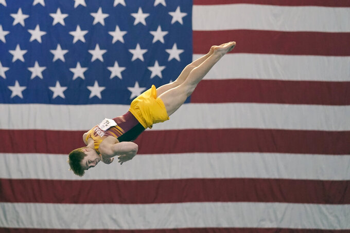 """Michael Moran, representing the University of Minnesota, competes during the Winter Cup gymnastics event Sunday, Feb. 28, 2021, in Indianapolis. A junior from Morristown, New Jersey, Moran admits there were people within his inner circle who discouraged him from competing collegiately because they viewed his chosen sport as a """"dying entity."""" The University of Minnesota and the University of Iowa will stop offering it as a scholarship sport at the end of the month. (AP Photo/Darron Cummings)"""