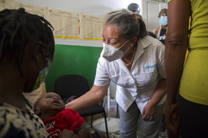 Jean Gough, UNICEF regional director for Latin America and the Caribbean, greets an infant in a malnutrition clinic in Les Cayes, Haiti, Wednesday, May 26, 2021. Gough visited the southern seaport amid concerns over an increase in malnutrition and a drop in childhood immunizations that officials blame on the coronavirus pandemic. (AP Photo/Joseph Odelyn)