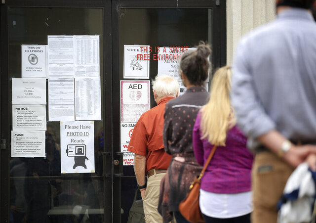 Voters stand in line Monday Oct. 19, 2020 at the Pulaski County Regional Building in downtown Little Rock, Ark.,  as they wait to vote on the first day of early voting. (Staton Breidenthal/The Arkansas Democrat-Gazette via AP)