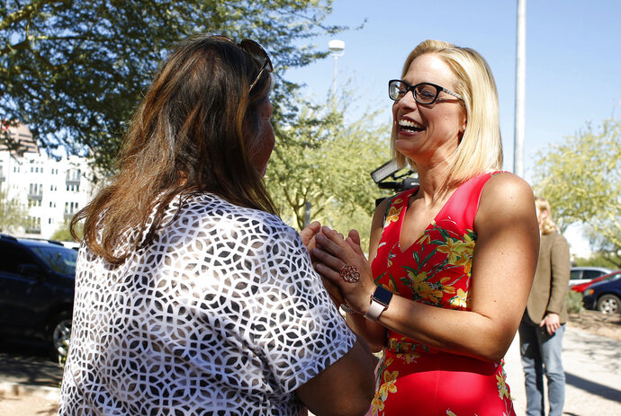 CORRECTS FROM SEN.-ELECT TO CANDIDATE- U.S. Senate candidate Kyrsten Sinema, D-Ariz., speaks to a supporter at the Barton Barr Central Library, Tuesday, Nov. 6, 2018, in Phoenix. Sinema and Republican challenger Martha McSally are seeking the senate seat being vacated by Jeff Flake, R-Ariz., who is retiring in January.(AP Photo/Rick Scuteri)