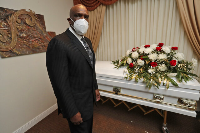 Andre Dawson poses for a photo at Paradise Memorial Funeral Home, Thursday, April 30, 2020, in Miami. For baseball Hall of Famer Andre Dawson, owning a funeral home has taken some getting used to. Now he's adjusting to life as a mortician in Miami during a global pandemic. He wears a mask and gloves, and explains to customers that services in the chapel must be shorter than normal and limited to 10 people.  (AP Photo/Wilfredo Lee)