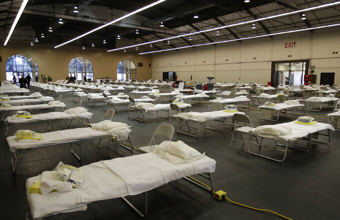 FILE - In this April 1, 2020, file photo, cots are set up at a possible COVID-19 treatment site in San Mateo, Calif. As tens of thousands of retired healthcare workers and medical and nursing students sign up for the newly established California Health Corps, almost nothing is known about how it will operate, how much it will cost and whether taxpayers will be liable for any malpractice. The volunteers are expected to work at places like the San Mateo County Event Center south of San Francisco, where hundreds of narrow beds have been set up six feet apart, the minimum health officials say is needed to avoid spreading the virus through a sneeze or cough. (AP Photo/Ben Margot, Pool, File)