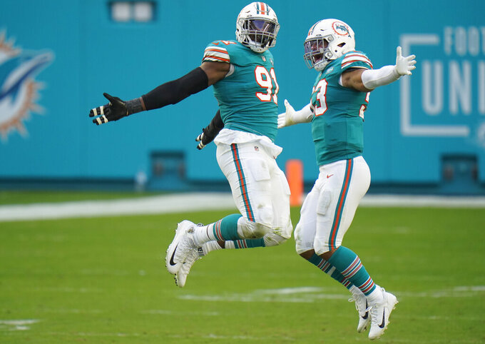 Miami Dolphins defensive end Emmanuel Ogbah (91) and middle linebacker Kyle Van Noy (53) celebrate after sacking New England Patriots quarterback Cam Newton during the second half of an NFL football game Sunday, Dec. 20, 2020, in Tampa, Fla. (AP Photo/Chris O'Meara)