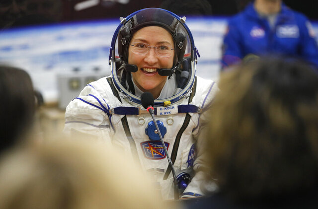 FILE - In this Thursday, March 14, 2019 file photo, U.S. astronaut Christina Koch, member of the main crew of the expedition to the International Space Station (ISS), speaks with her relatives through a safety glass prior the launch of Soyuz MS-12 space ship at the Russian leased Baikonur cosmodrome, Kazakhstan.  Koch told The Associated Press on Tuesday, Jan. 28, 2020, her 319th consecutive day in space _ that taking part in the first all-female spacewalk was the highlight of her mission. She's been living on the International Space Station since March and returns to Earth on Feb. 6, landing in Kazakhstan with two colleagues aboard a Russian capsule.  (AP Photo/Dmitri Lovetsky, Pool)