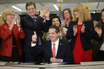 New York Gov. Andrew Cuomo, center, winks and gives a thumbs-up after signing the Child Victims Act in New York, Thursday, Feb. 14, 2019. Cuomo has signed into law long-sought legislation that extends the statute of limitations so sexual abuse victims can have more time to seek criminal charges or file lawsuits. (AP Photo/Seth Wenig)