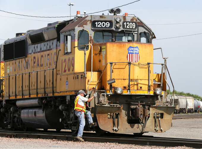 FILE - In this July 20, 2017, file photo, a Union Pacific employee climbs on board a locomotive in a rail yard in Council Bluffs, Iowa. One of Union Pacific's main unions is threatening to strike if the railroad doesn't do more to protect its employees from the coronavirus. (AP Photo/Nati Harnik, File)