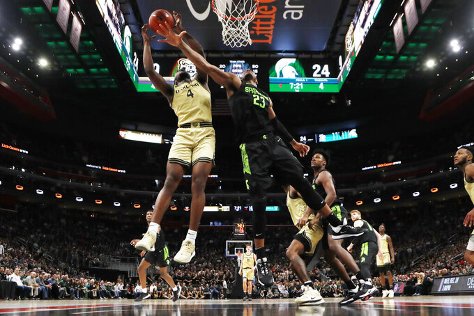 Michigan State forward Xavier Tillman (23) deflects a shot by Oakland forward Daniel Oladapo (4) during the first half of an NCAA college basketball game, Saturday, Dec. 14, 2019, in Detroit. (AP Photo/Carlos Osorio)