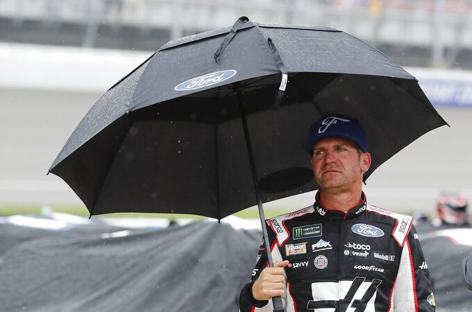 Clint Bowyer stands on pit row waiting out the rain delay during the NASCAR cup series auto race at Michigan International Speedway, Sunday, June 9, 2019, in Brooklyn, Mich. (AP Photo/Carlos Osorio)