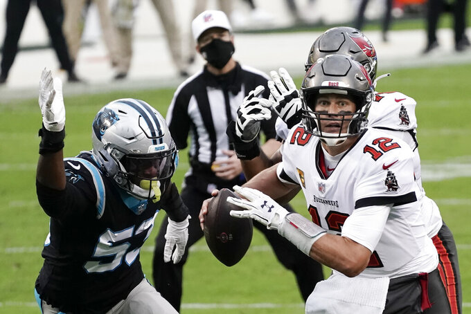 Tampa Bay Buccaneers quarterback Tom Brady (12) runs out of the pocket against Carolina Panthers defensive end Brian Burns (53) during the second half of an NFL football game, Sunday, Nov. 15, 2020, in Charlotte , N.C. (AP Photo/Gerry Broome)