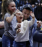 Golden State Warriors' Steph Curry laughs with his daughters, Riley Curry, left, and Ryan Curry, during halftime of an NCAA college basketball game between Oregon and California on Friday, Feb. 21, 2020, in Berkeley, Calif. (AP Photo/Ben Margot)