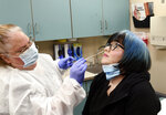 Nurse Jen Molstead, left, gives volunteer Melissa Harting of Harpersville, N.Y., a nasal swab test as the world's biggest study of a possible COVID-19 vaccine, developed by the National Institutes of Health and Moderna Inc., gets underway Monday, July 27, 2020, in Binghamton, N.Y. (AP Photo/Hans Pennink)