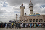 Wearing protective face masks, pilgrims from the Mouride Brotherhood pray outside the Grand Mosque of Touba during the celebrations of the Grand Magal of Touba, Senegal, Tuesday, Oct. 6, 2020. Despite the coronavirus pandemic, thousands of people from the Mouride Brotherhood, an order of Sufi Islam, gather for the annual religious pilgrimage to celebrate the life and teachings of Cheikh Amadou Bamba, the founder of the brotherhood. (AP Photo/Leo Correa)