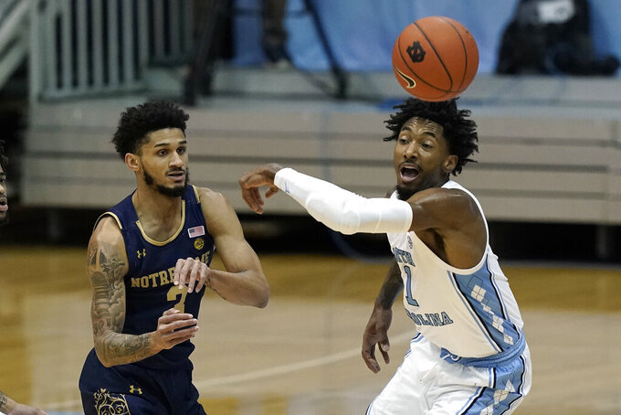 Notre Dame guard Prentiss Hubb (3) passes while North Carolina guard Leaky Black (1) defends during the first half of an NCAA college basketball game in Chapel Hill, N.C., Saturday, Jan. 2, 2021. (AP Photo/Gerry Broome)