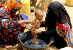 In this Aug. 25, 2018 photo, a severely malnourished infant is bathed in a bucket in Aslam, Hajjah, Yemen. Yemen's civil war has wrecked the impoverished country's already fragile ability to feed its population. Around 2.9 million women and children are acutely malnourished; another 400,000 children are fighting for their lives only a step away from starvation. (AP Photo/Hammadi Issa)