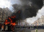 FILE - In this March 16, 2019 file photo, a news stand burns during a yellow vests demonstration on the Champs Elysees avenue in Paris. French President Emmanuel Macron will speak to the nation Monday April 15, 2019 to lay out his responses to the yellow vest crisis after three months of national debate meant to encourage ordinary people to propose changes to the country's economy and democracy. (AP Photo/Christophe Ena, File)