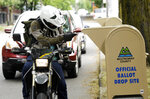 A voter drops off his ballot on the day of Oregon's primary election at a drive by drop-off station in Portland, Ore., Tuesday, May 15, 2018. (AP Photo/Don Ryan)