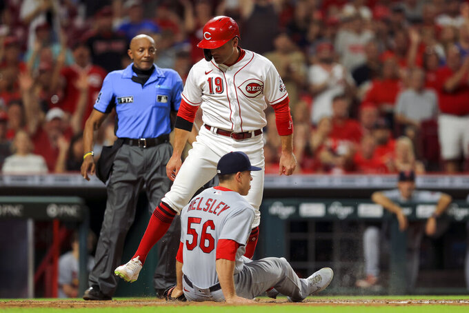 Cincinnati Reds' Joey Votto (19) scores a run on a wild pitch as St. Louis Cardinals' Ryan Helsley fields the ball during the seventh inning of a baseball game in Cincinnati, Friday, July 23, 2021. (AP Photo/Aaron Doster)