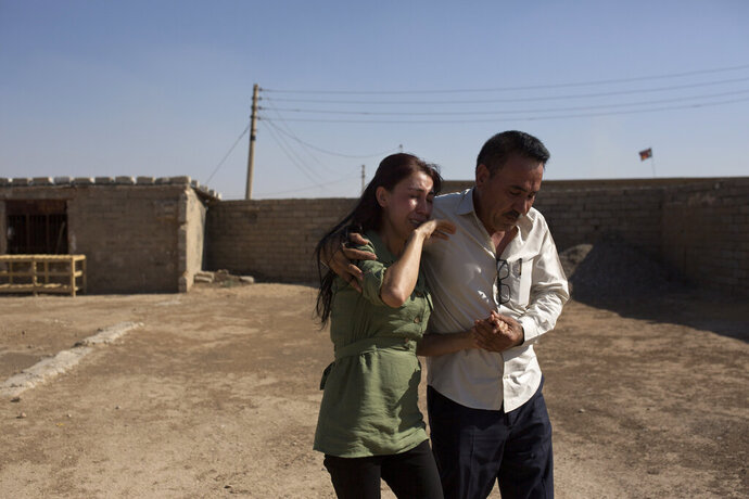 In this Aug. 31, 2019 photo, Layla Taloo is overcome with grief as her brother, Khalid, leads her away from the compound where she last saw her husband in 2014 after the family was captured by Islamic State militants, in Tal Afar, Iraq. Her family was taken to a village with nearly 2,000 other Yazidis forced to convert to Islam, before the men were taken away. Their bodies were never found, but they are believed to have been thrown into a nearby sinkhole. (AP Photo/Maya Alleruzzo)