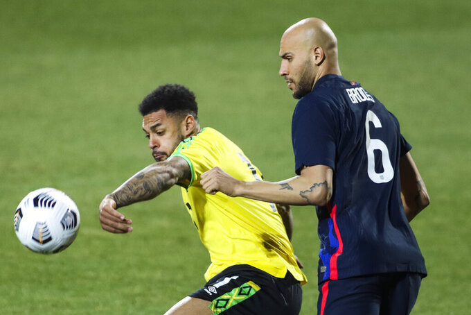 USA's John Brooks, right, duels for the ball with Jamaica's Andre Gray during the international friendly soccer match between USA and Jamaica at SC Wiener Neustadt stadium in Wiener Neustadt, Austria, Thursday, March 25, 2021. (AP Photo/Ronald Zak)