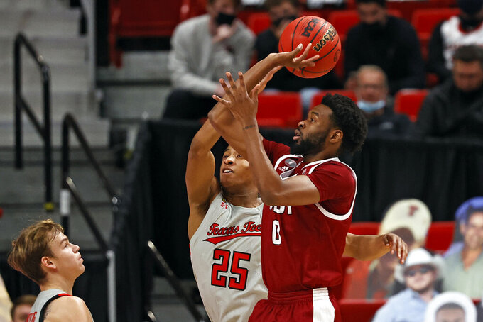 Texas Tech's Nimari Burnett (25) blocks the shot by Troy's Kieffer Punter (0) during the first half of an NCAA college basketball game Friday, Dec. 4, 2020, in Lubbock, Texas. (AP Photo/Brad Tollefson)