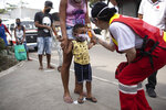 A member of the Red Cross checks the temperature of a child at the CEASA, Rio de Janeiro's main wholesale market, amid the new coronavirus pandemic in Rio de Janeiro, Brazil, Tuesday, June 23, 2020. (AP Photo/Silvia Izquierdo)