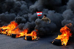 An anti-government demonstrator jumps on tires that were set on fire to block a main highway as he holds a national flag, during a protest in the town of Jal el-Dib, north of Beirut, Lebanon, Tuesday, Jan. 14, 2020. Following a brief lull, Lebanese protesters returned to the streets, blocking several roads around the capital, Beirut, and other areas of the country on Tuesday in renewed rallies against a ruling elite they say has failed to address the economy's downward spiral. (AP Photo/Bilal Hussein)