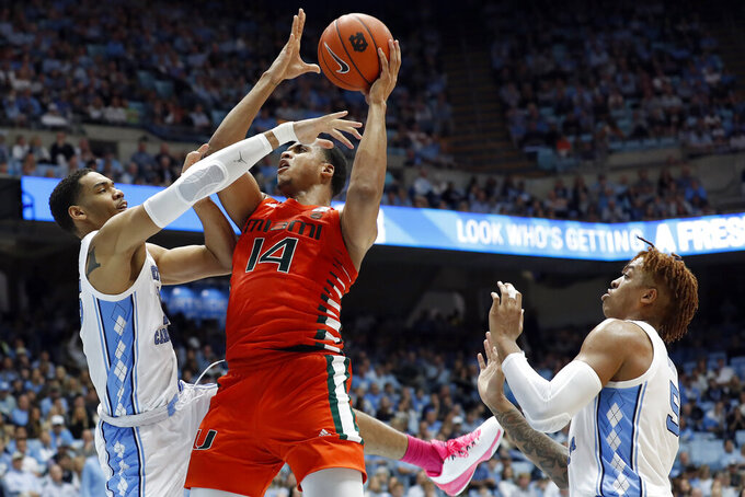 North Carolina forward Garrison Brooks, left, and forward Armando Bacot, right, defend against Miami center Rodney Miller Jr., center, during the second half of an NCAA college basketball game in Chapel Hill, N.C., Saturday, Jan. 25, 2020. (AP Photo/Gerry Broome)