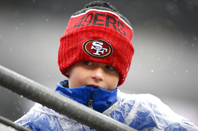A young fans waits in the rain for players to take the field before the start of an NFL football game between the Baltimore Ravens and the San Francisco 49ers, Sunday, Dec. 1, 2019, in Baltimore, Md. (AP Photo/Nick Wass)