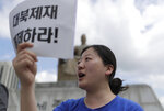 A protester shouts slogans during a rally demanding the peace on the Korean peninsula and to stop sanctions on North Korea, ahead of U.S. President Donald Trump's scheduled visit, near the U.S. embassy in Seoul, South Korea, Thursday, June 27, 2019. North Korea said Thursday South Korea must stop trying to mediate between Pyongyang and Washington. The North's Foreign Ministry also repeated its demand that the United States must work out mutually acceptable proposals to salvage a deadlocked nuclear negotiations by the end of December. The sign held by the protester reads: