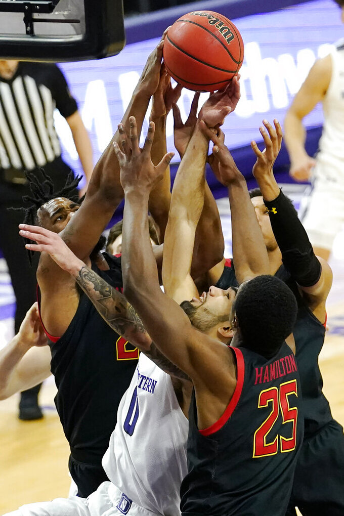 Northwestern guard Boo Buie, center, battles for a rebound against Maryland forward Donta Scott, left, forward Jairus Hamilton, right, and guard Aaron Wiggins during the second half of an NCAA college basketball game in Evanston, Ill., Wednesday, March 3, 2021. (AP Photo/Nam Y. Huh)