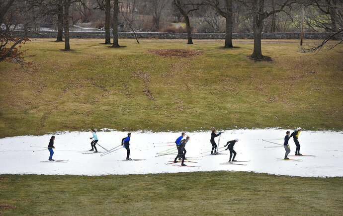 FILE - In this Dec. 11, 2016 file photo, St. Cloud Cathedral/Sartell Nordic ski team members practice on a track of man-made snow at Riverside Park in St. Cloud, Minn., where lack of snow in the area made it difficult for teams to practice. Since 1970, Minnesota's winters have been warming at a rate of more than 1 degree a decade. State residents notice the change, and say winter isn't as cold as it used to be and the snow is less predictable. (Dave Schwarz/St. Cloud Times via AP, File)