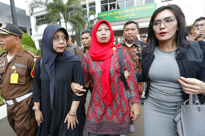 Baiq Nuril Maknun, center, arrives at the Attorney General's office in Jakarta, Indonesia. Friday, July 12, 2019. Maknun facing six month in prison in Indonesia for recording her boss's sexual harassment is expected to receive a presidential amnesty after an outcry over the sentence. Attorney-General Muhammad Prasetyo said Friday he suspended enforcement of the sentence and a 500 million rupiah ($35,000) fine that was recently upheld by the Supreme Court. (AP Photo/Tatan Syuflana)