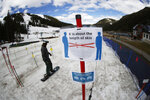FILE - In this May 27, 2020, file photo, a sign reminds skiers and snowboarders to practice social distancing while wearing a face covering in lift lines at the reopening of Arapahoe Basin Ski Resort, which closed in mid-March to help in the effort to stop the spread of the new coronavirus, in Keystone, Colo. Colorado health officials are weighing in on how to safely navigate the upcoming ski season amid a pandemic as eager skiers and snowboarders who have been cooped up for the greater part of a year prepare to hit the slopes in a matter of weeks. The state released guidance Monday, Oct. 19, after gathering feedback from resorts and county health officials. (AP Photo/David Zalubowski, File)