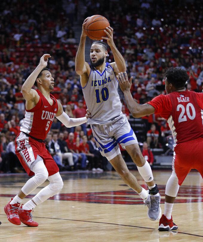 Nevada's Caleb Martin drives between UNLV's Noah Robotham, left, and Nick Blair during the second half of an NCAA college basketball game Tuesday, Jan. 29, 2019, in Las Vegas. Nevada won 87-70. (AP Photo/John Locher)